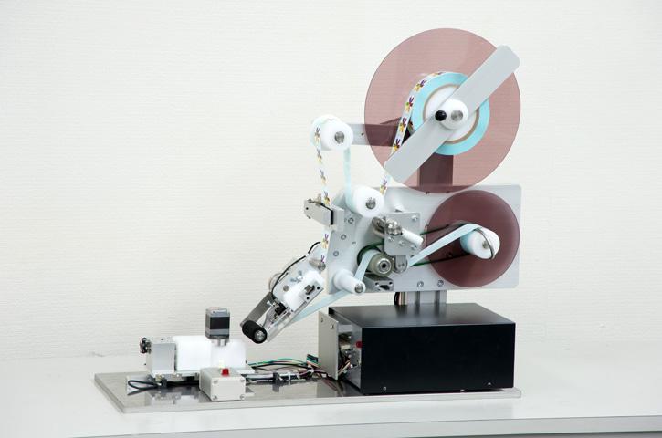 特殊形状用ラベラーQTL-100はユニークな形状に対してラベルを貼ります